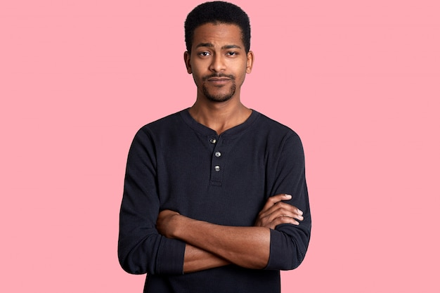 Młody ciemnoskóry mężczyzna o spokojnym wyrazie twarzy, krótkiej fryzurze i brodzie, ubiera swobodną koszulę i trzyma skrzyżowane ręce. czarny samiec, pozy odizolowywać nad różową ścianą. koncepcja ludzi.