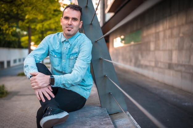 Młody ciemnowłosy kaukaski mężczyzna w dżinsowej koszuli w mieście