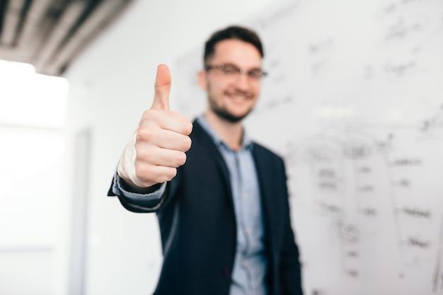 Młody ciemnowłosy mężczyzna w okularach stoi w pobliżu tablicy w biurze. nosi niebieską koszulę i ciemną kurtkę. skoncentruj się na przedniej stronie jego znaku ręką.