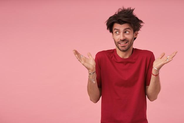 Młody ciemnowłosy mężczyzna z brodą, stojący w czerwonej koszulce, spoglądający na bok ze zdziwioną twarzą i unoszący dłonie do góry, ściągający czoło i unoszący brwi
