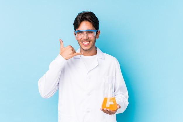 Młody cientific kaukaski mężczyzna na białym tle przedstawiający telefon komórkowy gest z palcami.