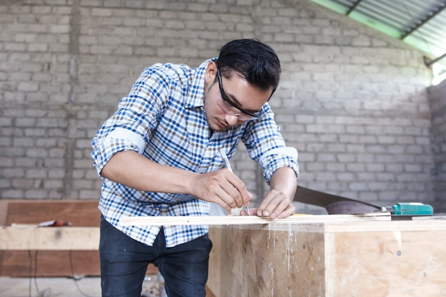 Młody cieśla mierzy drewnianą deskę i zaznacza