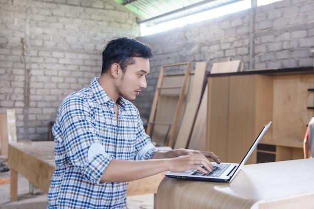Młody cieśla pracuje na jego laptopie