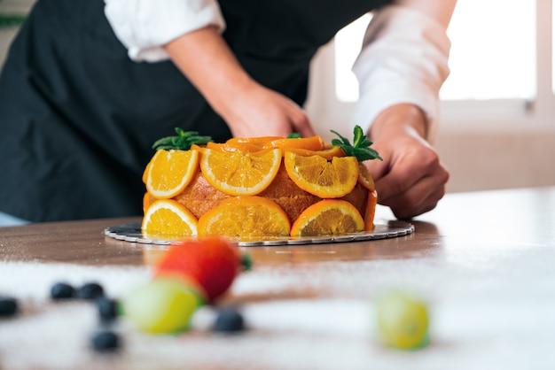 Młody cukiernik gotuje ciasto pomarańczowe z pokrojonymi pomarańczami