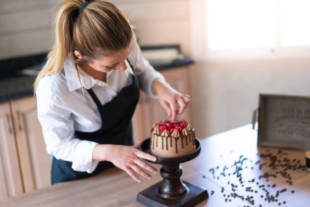 Młody cukiernik gotuje pyszne domowe ciasto czekoladowe z owocami w kuchni