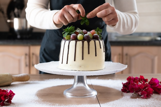 Młody cukiernik gotuje w kuchni pyszne domowe ciasto czekoladowe z owocami
