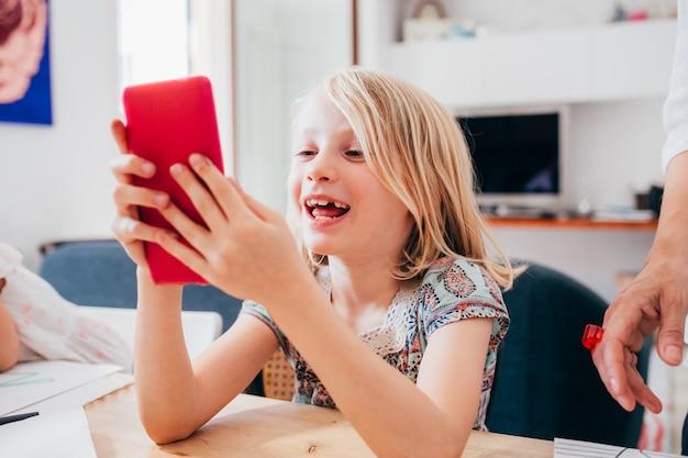 Młody cyfrowy rodzimych kobiet dziecko kryty w domu przy użyciu telefonu