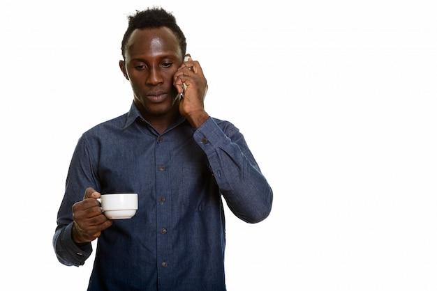 Młody czarnego afrykanina mężczyzna opowiada na telefonie komórkowym podczas gdy trzymający filiżankę
