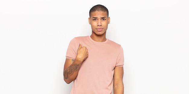 Młody czarnoskóry mężczyzna czuje się zdezorientowany, zdziwiony i niepewny, wskazując na siebie zastanawiającego się i pytając kogo, ja?