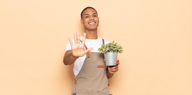 Młody czarnoskóry mężczyzna uśmiechający się i wyglądający przyjaźnie, pokazujący cyfrę piątą lub piątą z ręką do przodu, odliczający w dół