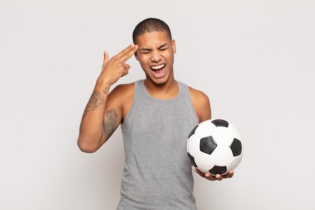 Młody czarnoskóry mężczyzna wyglądający na nieszczęśliwego i zestresowanego, samobójczy gest wykonujący znak pistoletu ręką, wskazujący na głowę