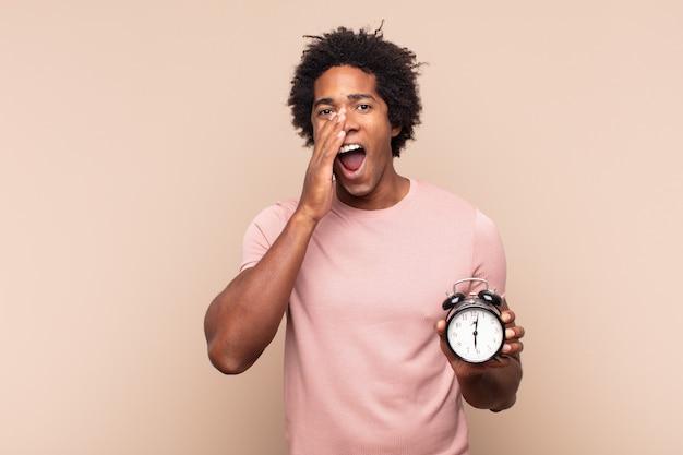 Młody czarny afro czuje się szczęśliwy, podekscytowany i pozytywny, krzyczy głośno z rękami przy ustach i woła