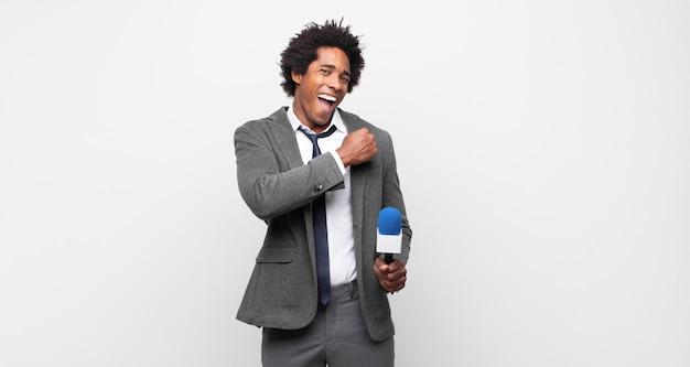 Młody czarny afro czuje się szczęśliwy, pozytywnie nastawiony i odnosi sukcesy, zmotywowany, gdy staje przed wyzwaniem lub świętuje dobre wyniki
