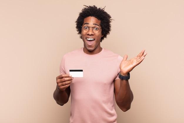 Młody czarny afro czuje się szczęśliwy, zaskoczony i wesoły, uśmiecha się pozytywnie, realizuje rozwiązanie lub pomysł