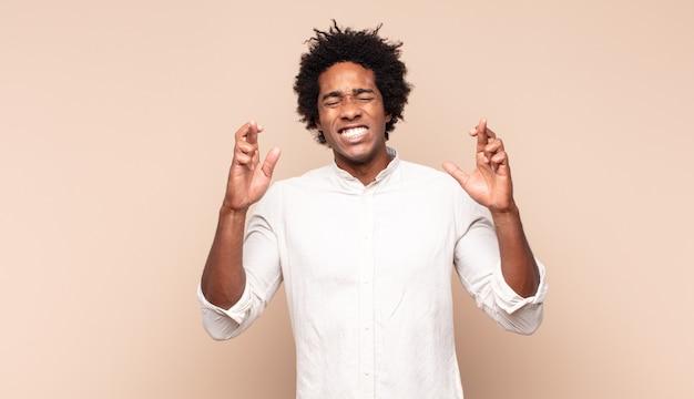 Młody czarny afro czuje się zdenerwowany i pełen nadziei, krzyżuje palce, modli się i ma nadzieję na szczęście