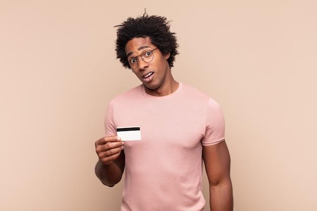 Młody czarny afro czuje się zdziwiony i zdezorientowany, z głupim, oszołomionym wyrazem twarzy, patrząc na coś nieoczekiwanego