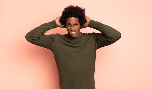 Młody czarny afro czuje się zestresowany, zmartwiony, niespokojny lub przestraszony, z rękami na głowie, panikuje podczas pomyłki