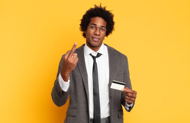 Młody czarny afro czuje się zły, zirytowany, zbuntowany i agresywny, macha środkowym palcem, walczy