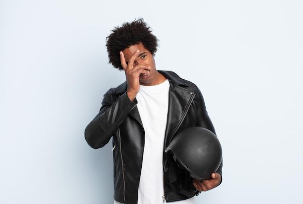 Młody czarny afro czuje się znudzony, sfrustrowany i senny po męczącym, nudnym i żmudnym zadaniu, trzymając twarz ręką