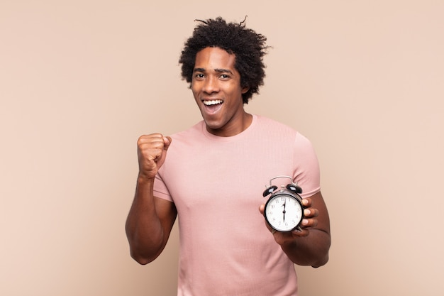 Młody czarny afro czuje się zszokowany, podekscytowany i szczęśliwy, śmieje się i świętuje sukces, mówiąc wow!