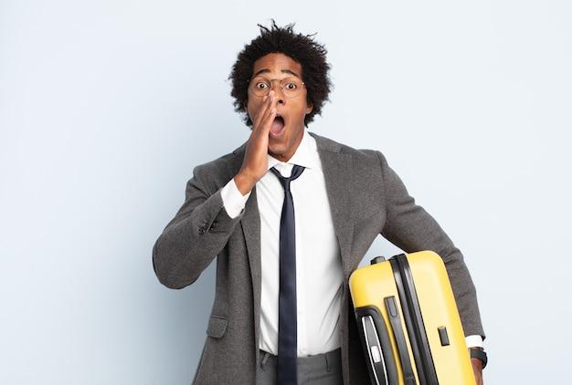 Młody czarny afro mężczyzna czuje się szczęśliwy, podekscytowany i pozytywnie nastawiony, wydaje wielki okrzyk z rękami przy ustach, wołając