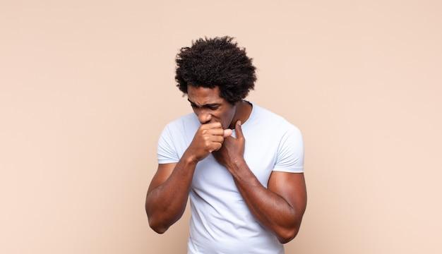 Młody czarny afro mężczyzna czuje się szczęśliwy, podekscytowany, zaskoczony lub zszokowany, uśmiechnięty i zdumiony czymś niewiarygodnym