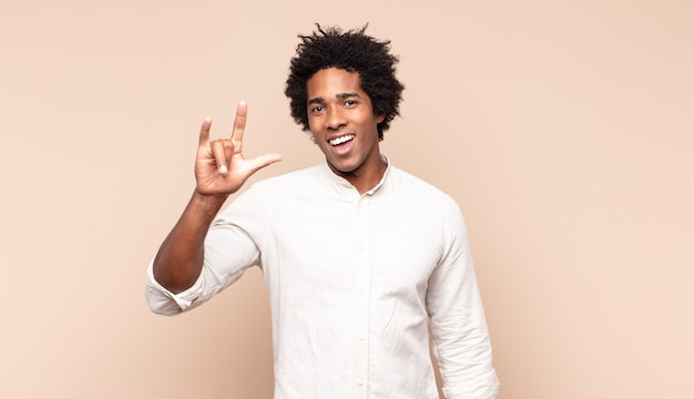 Młody czarny afro mężczyzna czuje się szczęśliwy, zabawny, pewny siebie, pozytywny i zbuntowany, wykonując ręką rockowy lub heavy metalowy znak