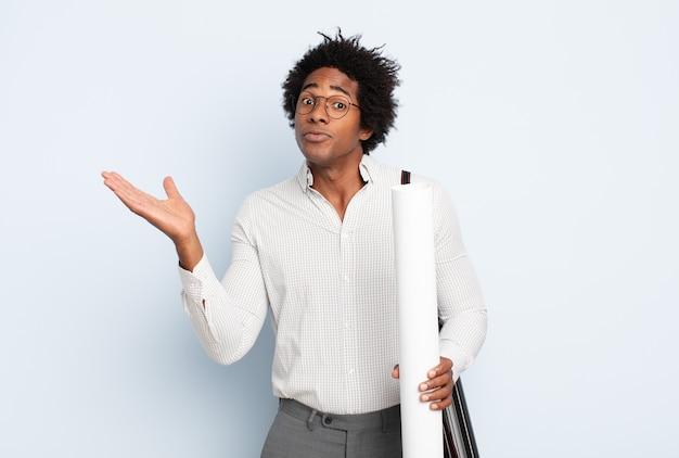 Młody czarny afro mężczyzna czuje się zdezorientowany i zdezorientowany