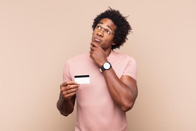 Młody czarny afro mężczyzna myślący, mający wątpliwości i zdezorientowany, mający różne możliwości, zastanawiający się, którą decyzję podjąć