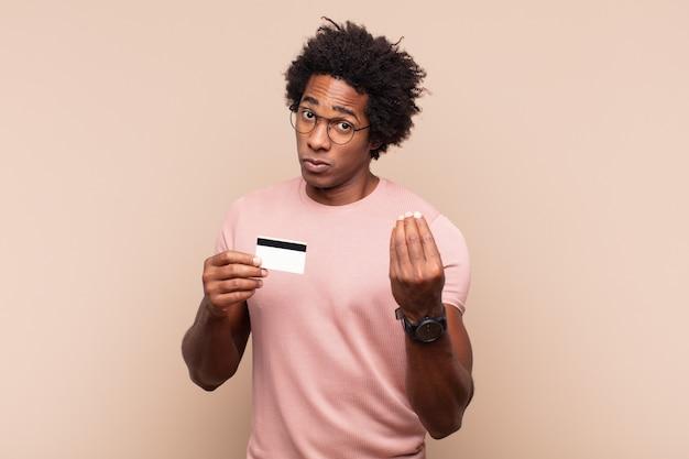 Młody czarny afro mężczyzna robiący kaprys lub gest pieniędzy, mówiąc ci, żebyś spłacił swoje długi!