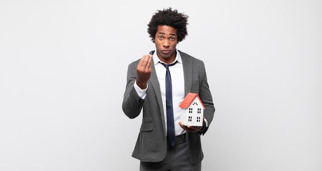 Młody czarny afro mężczyzna robiący kaprys lub gest pieniędzy, mówiący, żebyś spłacił swoje długi!
