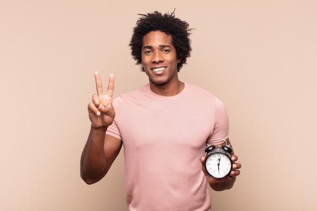 Młody czarny afro mężczyzna uśmiecha się i wygląda przyjaźnie, pokazując numer dwa lub sekundę z ręką do przodu, odliczając w dół