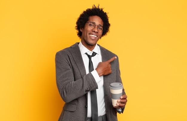 Młody czarny afro mężczyzna uśmiecha się radośnie, czuje się szczęśliwy i wskazuje na bok i w górę