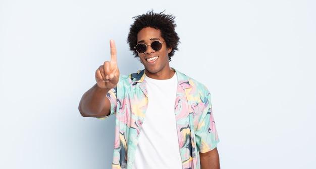 Młody czarny afro mężczyzna uśmiechający się dumnie i pewnie, triumfalnie tworząc pozę numer jeden, czując się jak lider
