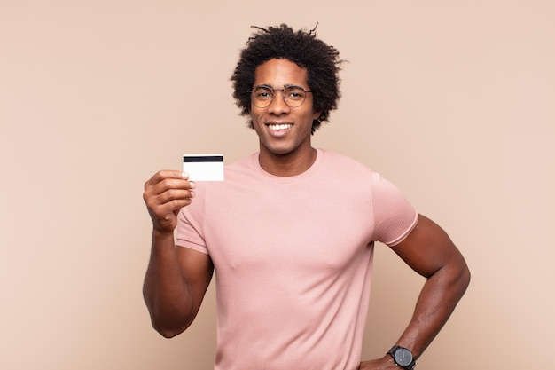 Młody czarny afro mężczyzna uśmiechający się radośnie z ręką na biodrze i pewny siebie, pozytywny, dumny i przyjazny