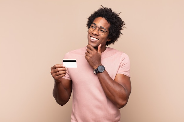 Młody czarny afro mężczyzna uśmiechający się ze szczęśliwym, pewnym siebie wyrazem twarzy z ręką na brodzie, zastanawiając się i patrząc w bok