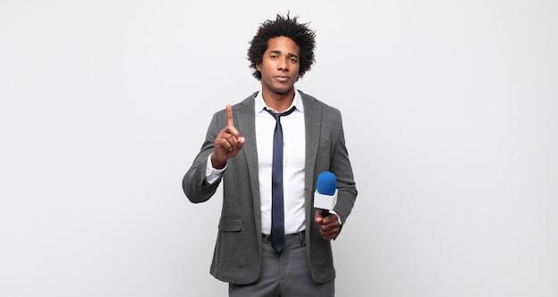 Młody czarny afro mężczyzna uśmiechnięty i wyglądający przyjaźnie, pokazujący numer jeden lub pierwszy z ręką do przodu, odliczający