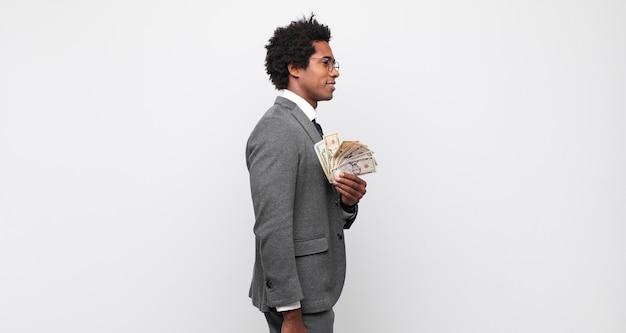 Młody czarny afro mężczyzna w widoku profilu, który chce skopiować przestrzeń do przodu, myśląc, wyobrażając sobie lub marząc