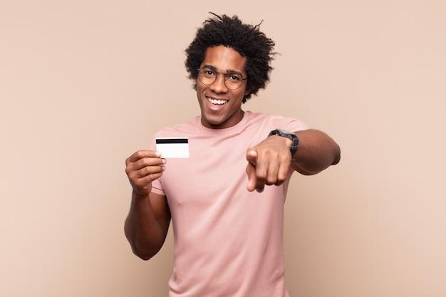 Młody czarny afro mężczyzna wskazujący na aparat z zadowolonym, pewnym siebie, przyjaznym uśmiechem, wybierający ciebie