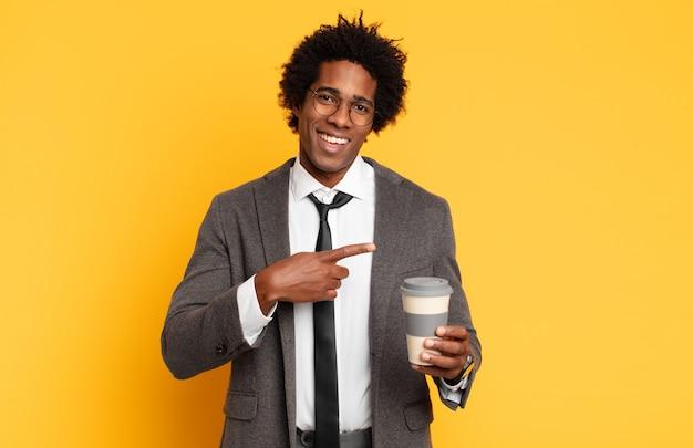 Młody czarny afro mężczyzna wygląda na podekscytowanego i zaskoczonego, wskazując na bok i w górę, aby skopiować przestrzeń