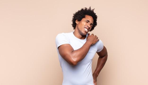 Młody czarny afro mężczyzna wyglądający na smutnego, zranionego i załamanego, trzymającego obie ręce blisko serca, płaczącego i przygnębionego