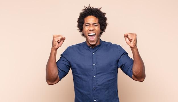 Młody czarny afro mężczyzna wyglądający na szczęśliwego i przyjaznego, uśmiechnięty i mrugający okiem z pozytywnym nastawieniem