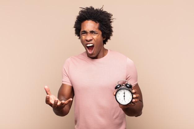 Młody czarny afro mężczyzna wyglądający na wściekłego, zirytowanego i sfrustrowanego, krzyczący wtf lub co jest z tobą nie tak