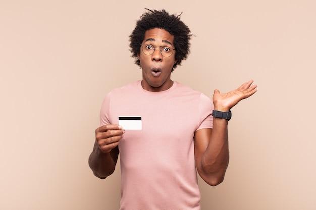 Młody czarny afro mężczyzna wyglądający na zaskoczonego i zszokowanego, z opuszczoną szczęką, trzymając przedmiot z otwartą ręką na boku