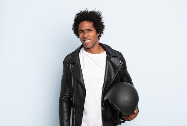 Młody czarny afro mężczyzna wyglądający na zdziwionego i zdezorientowanego, przygryzający wargę nerwowym gestem, nie znający odpowiedzi na problem