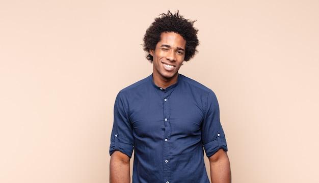Młody czarny afro mężczyzna wyglądający na zestresowanego i sfrustrowanego, pracujący pod presją, ból głowy i kłopoty
