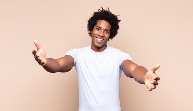 Młody czarny afro mężczyzna wyglądający poważnie i krzyżowo