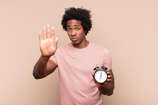 Młody czarny afro mężczyzna wyglądający poważnie, surowo, niezadowolony i zły, pokazując otwartą dłoń wykonujący gest stopu