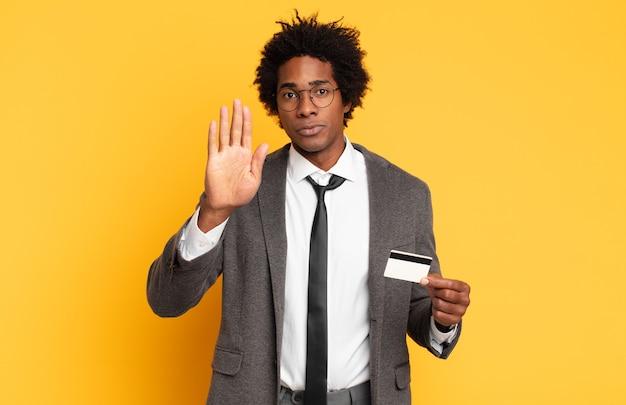 Młody czarny afro mężczyzna wyglądający poważnie, surowo, niezadowolony i zły, pokazujący otwartą dłoń wykonujący gest stopu