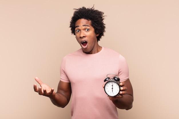Młody czarny afro mężczyzna z otwartymi ustami i zdumiony, zszokowany i zdumiony niewiarygodną niespodzianką